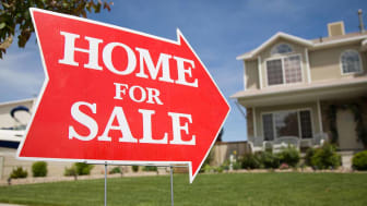 "An arrow shaped red ""Home For Sale"" sign in front of a suburban 2-story home.The green grass and blue sky is visible in the background."