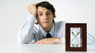picture of young man impatiently sharing at hourglass