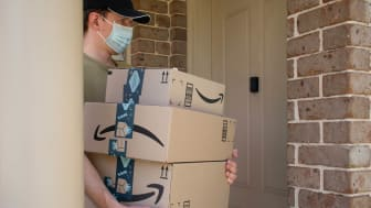 An Amazon delivery driver brings packages to a residential front door