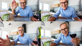 A senior man enjoys a glass of wine during a happy hour chat on Zoom.