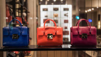 Three luxury handbags at a store.