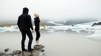 Asian girl wearing woolly hat and winter boots and hooded man stand on rocks near the edge of a lake in the Jokulserlon glacier in Vatnajokull National Park, Iceland, with icebergs on the bac