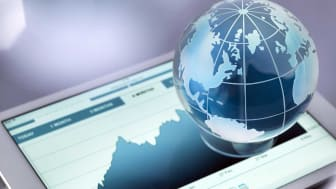A glass globe illustrating the world sitting on a digital table showing an increase in stock price.