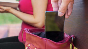 Pickpocket thief is stealing smartphone from bag of a woman reading book.
