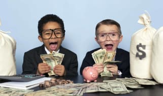 Two cute kids all dressed up like big Wall Street hot shots, with big, excited faces, holding money and sitting at a table with bags of money.