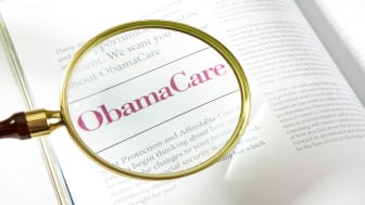 picture of a magnifying glass over a book about ObamaCare