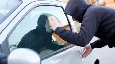 A thief peers into a car window