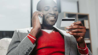 A man reads a credit card while talking on a smart phone