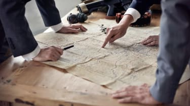 Three men in suits discussing plans while looking at a map lying on a table