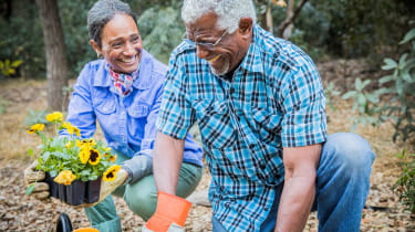A couple smiles while gardening.