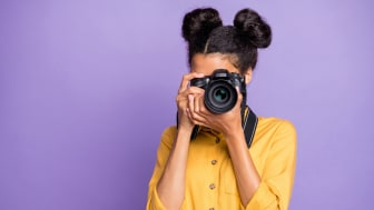 Photo of a woman taking a photo with a single lens reflex camera