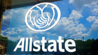 Window of an Allstate storefront reflecting a bright, partly cloudy sky
