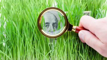 Looking through a magnifying glass at a $100 dollar bill hiding in grass