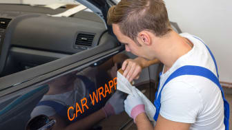 A worker puts an advertisement on the passenger side of a car