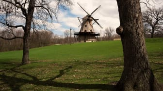 A windmill sits idly in the background of a park in Geneva, Ill.