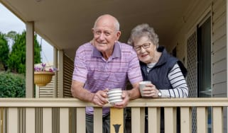 Senior couple having coffee on their front porch