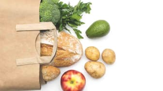 Top view paper bag of different fresh health food on white background.