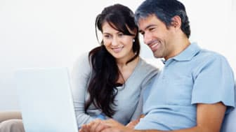 Mature couple working on laptop and smiling
