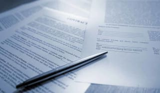 A blue tinted image of silver ball point pen lying on scattered legal contract documents on a wooden table, ready to sign to complete the deal. This conceptual image is shot with a shallow de