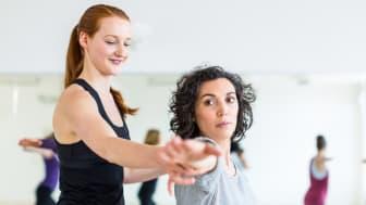 A yoga teacher adjusts a student's pose.
