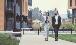 A man and a woman walk through an apartment community, evaluating it as they go..