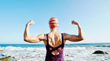 A woman flexes her muscles.