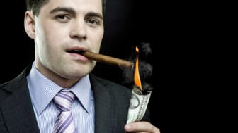 picture of rich guy lighting cigar with a dollar bill
