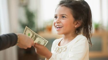 A smiling child accepts a gift of a dollar bill