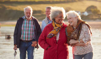 Two senior couples walking and talking along a beach