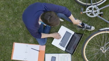 Overhead view college student studying with laptop grass