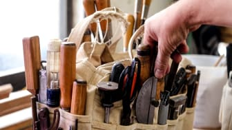 A hand reaches into a tool pouch