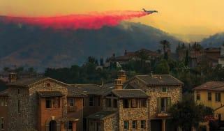 firefighting plane flying over house
