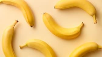 Six yellow bananas on a tabletop