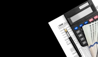 Tax forms, a calculator and a pen on a black background.