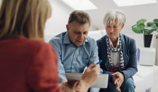 Mature Couple Meeting with Financial Advisor, selective focus to senior man and mature woman listening to financial advisor. She is pointing with pen to digital tablet and speaking about reti
