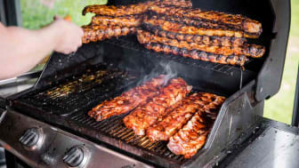 A young man is busy grilling a mound of mouthwatering baby back ribs on a large smoker grill in Jondal, Norway.