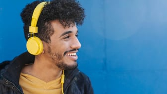 Portrait of young man smiling and listening to music with yellow headphones with a blue wall in the background.