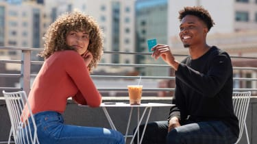 Photo of a young woman and a young man having iced coffee outside. The man is holding up a credit card.