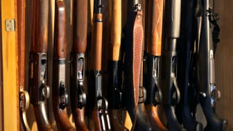 A picture of a gun collection in a cabinet