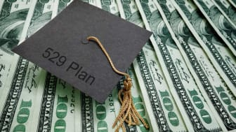 picture of graduation cap sitting on money