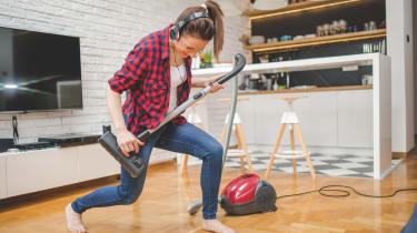 One woman, using vacuum cleaner for cleaninig her house, singing and dancing.