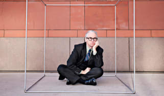 An unhappy businessman wearing a suit sits cross-legged inside a box.