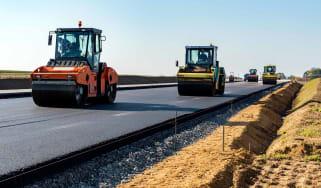 steamrollers repair a road