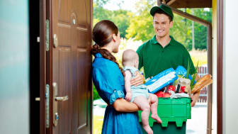 Delivery man standing at the door of the house and carrying box with groceries, talking with woman holding baby.