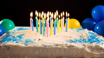 A sheet cake with lit birthday candles