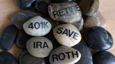 Smooth rocks with the words retire, 401K, IRA, roth and save on them arranged in a zen-like way.
